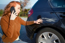 Woman reporting car accident event calling on the phone