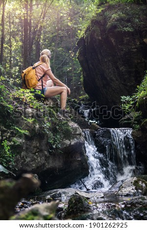 Woman resting during hike in wonderful nature. Hiker sitting on rock near a stream in forest at natural parkland Mala Fatra, Slovakia Stock photo ©