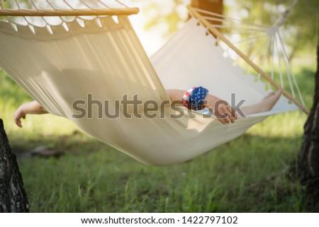 Woman resting in hammock outdoors. Sleeping outdoors.