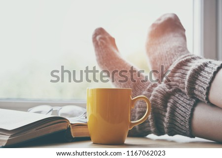 Woman resting keeping legs in warm socks on table with morning coffee and reading book Foto d'archivio ©