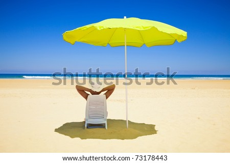 woman resting under umbrella facing the seaside in a deserted beach with deep blue sky