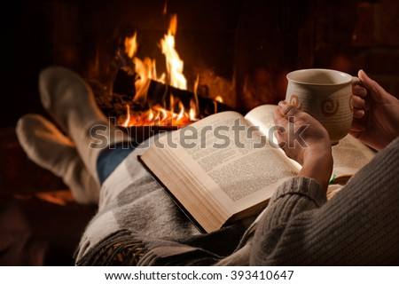 Woman resting with cup of hot drink and book near fireplace #393410647