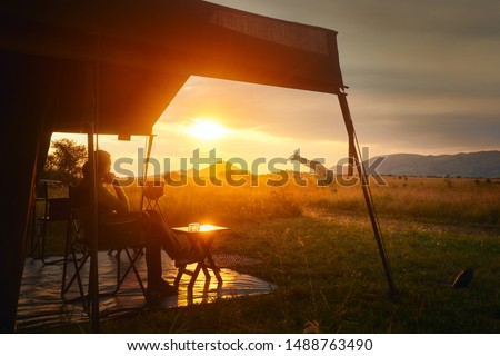 Woman rests after safari in luxury tent during sunset camping in the African savannah of Serengeti National Park, Tanzania.Woman Camping Tent Savanna Outdoors Concept