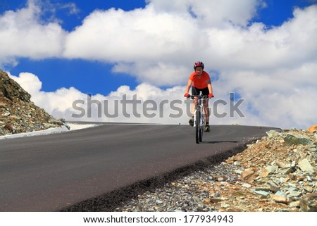 Woman rides a bike on mountain road in summer #177934943