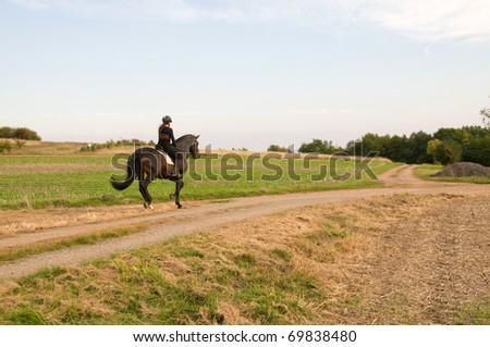 Woman rides at a gallop on a brown horse.