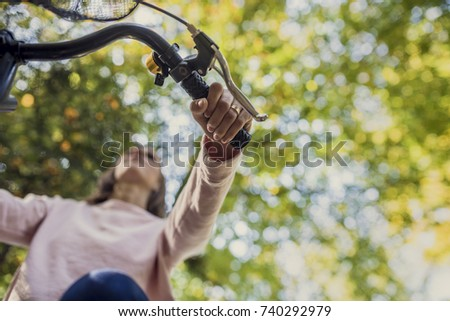 Woman riding a bicycle viewed from below looking up at her hand on the handle bars against green trees.