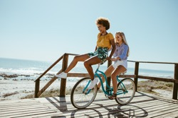 Woman riding a bicycle with her friend sitting on the handlebar. Two girls on bike ride having great fun.
