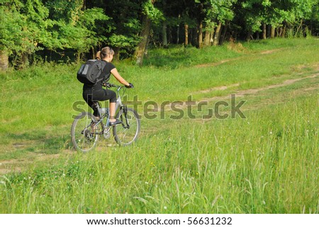 woman riding a bike on a road in forest. it has a bit motion blur