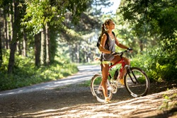 Woman riding a mountain bike in the forest.