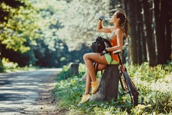 Woman riding a mountain bike in the forest.She  resting ,making pause.