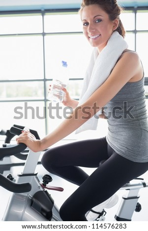 Woman riding an exercise bike and drinking a bottle of water