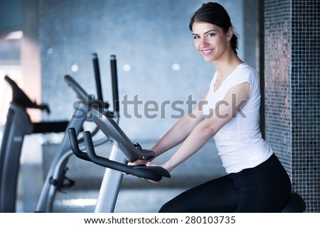 Woman riding an exercise bike in gym.Doing sport biking in the gym for fitness.Cardio and fat loss workout in the gym.Athletic woman pedaling on a stationary bike.Sport and fitness,summer body goals