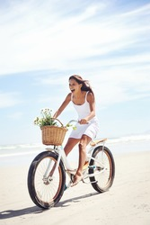 woman riding bicycle on beach in summer