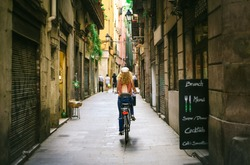 Woman riding bicycle through old street of Barcelona