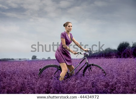 woman riding bike through a field of lilac flowers