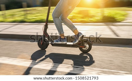 woman riding black electric kick scooter at cityscape at summer, motion blur