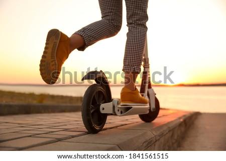 Woman riding electric kick scooter outdoors at sunset, closeup