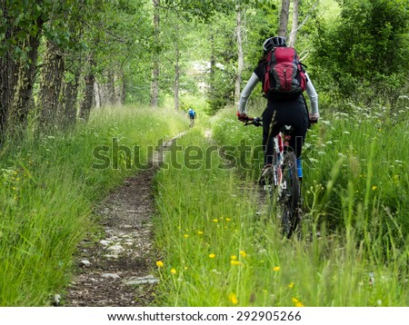 Woman riding mountain bike on a dirt road in the forest.
