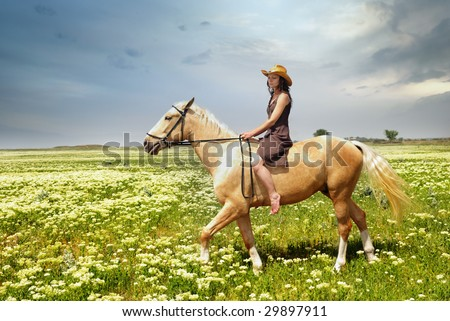 Woman riding on a horseback in the field with green grass