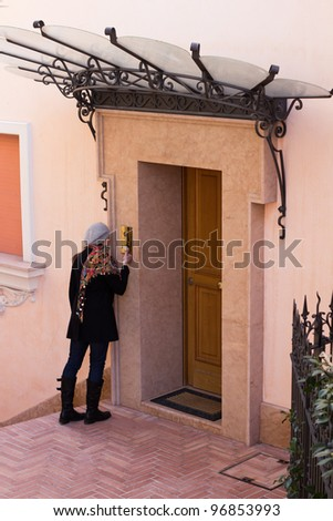 Woman Ringing The Entrance Door To A Modern Luxurious Flat