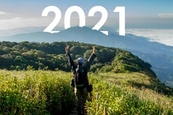 Woman rised arms up on top of mountain with 2021 year at behind. Out door travel, new destination, plan and successful concept.