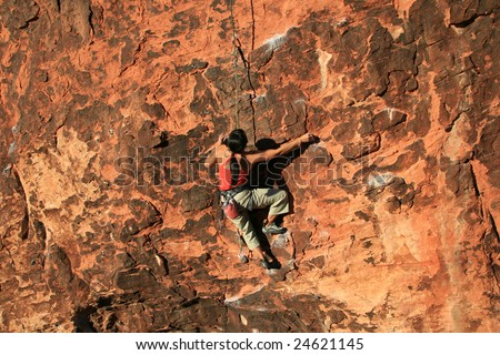 woman rock climber in red climbing a red sandstone cliff at Red Rocks, Nevada