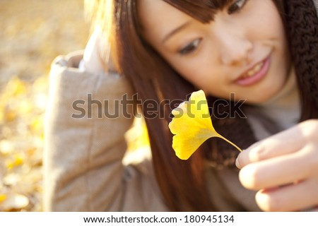 woman rolling on a pile of ginkgo leaves, #180945134