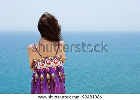 Woman rotated back looking at sea panorama view
