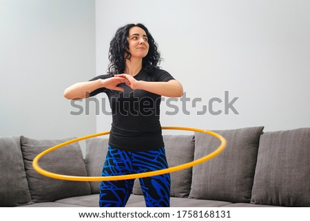 Woman rotating hula hoop. Girl training at home. Healthy sporty lifestyle. Woman doing workout and works with hula hoop. Happy fitness woman. Waist building and weight loss concept.