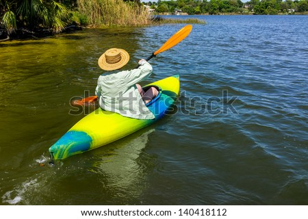 Woman rowing away from shore in her kayak on a beautiful river or lake.