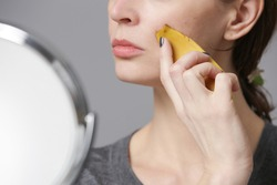 Woman rubbing banana peel on her face to brighten and hydrate skin and reduce wrinkles. Zero waste and natural skin care concept.