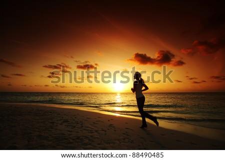 woman run along the sea coast of sunrise behind