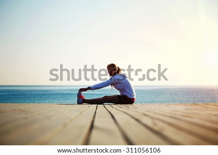 Woman runner doing exercises for the muscles of the body after an active run