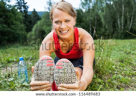 Woman runner exercising and stretching, summer nature outdoors. Female athlete working out on grass, activity and exercise