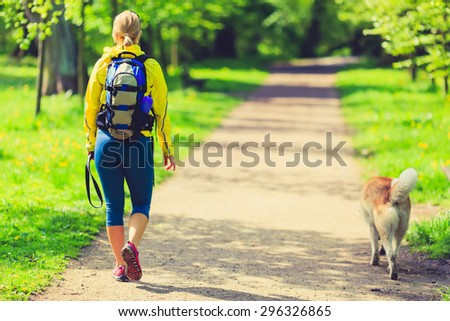 Woman runner running and walking with dog in park, summer nature, exercising in bright forest outdoors