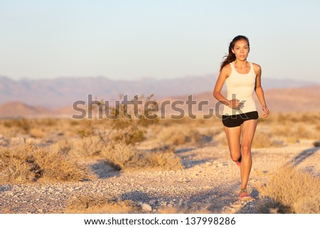 Woman runner running cross country trail run. Female jogger training outside on path outdoors at summer sunset. Beautiful young fitness model with healthy lifestyle . Mixed race Asian Caucasian girl.