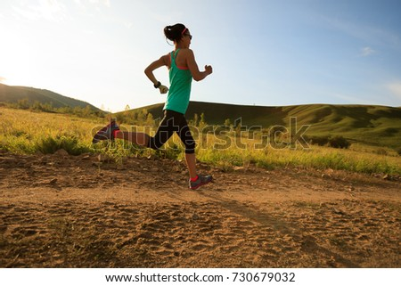woman runner running on forest trail #730679032
