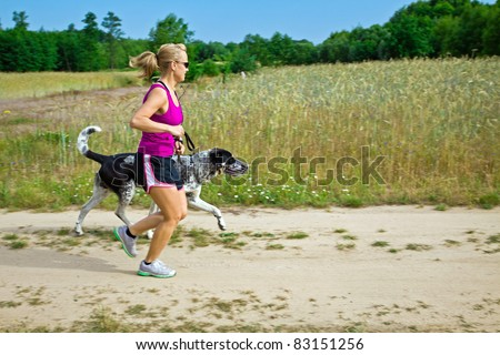 Woman runner running with a dog on country road