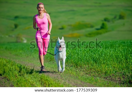 Woman runner running with dog on country road in summer nature, fitness and exercising outdoors, motion blur. Cross country running with friend.
