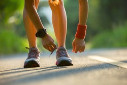 woman runner tying shoelace before run on forest trail