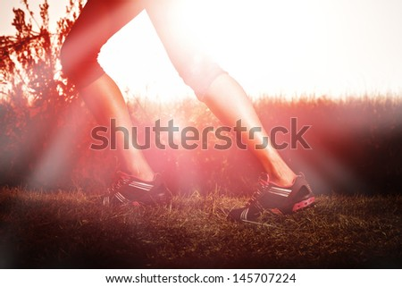 woman running at sunrise with muscular legs