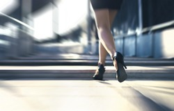Woman running away or walking fast with high heels in city street. Busy business person in hurry. Late from work or stress fast. Sprint stairs. Scared terrified lady being chased. Motion blur.