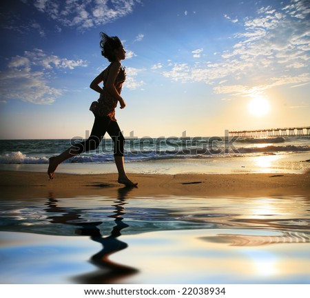 Woman running by the ocean beach at sunset
