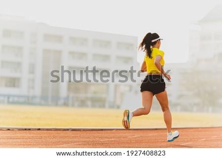 woman running during sunny morning on stadium track Сток-фото ©