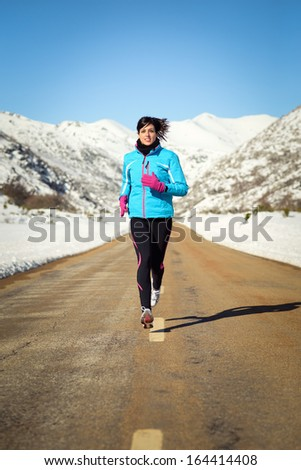 Woman running fast in country winter mountain road Female runner training endurance outdoor in cold weather