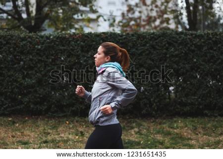 Woman running. Female runner jogging, training for marathon. Fit girl fitness athlete model exercising outdoor. #1231651435