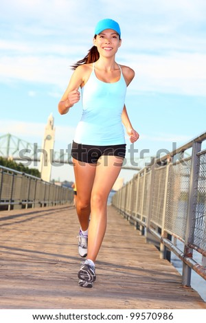 Woman running. Female runner training outside on sunny summer day in Montreal Old Port, Montreal, Quebec, Canada. Mixed race Asian / Caucasian female fitness sports model outside. - stock photo
