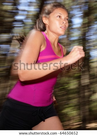 Woman running in forest motion blurred. Asian Caucasian athlete.