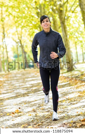 Woman running in park. Female athlete jogging on autumn day. Sport fitness brunette model training outdoor.
