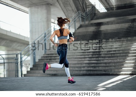 Woman running in urban environment. Back view